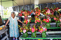 A local auntie sells flower arrangements of anthuriums, orchids and other tropical plants at a booth at the Hilo Farmers Market, Big Island of Hawai'i.