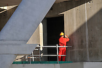 Construction worker fixing the cement outer wall of a new building in Marseille, France.