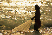 Hawaiian man with his throw net on the ocean's edge at sunset.