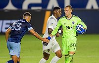 CARSON, CA - OCTOBER 18: Evan Bush #30 GK of the Vancouver Whitecaps low fives team mate Ali Adnan #53 during a game between Vancouver Whitecaps and Los Angeles Galaxy at Dignity Heath Sports Park on October 18, 2020 in Carson, California.