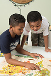 Brothers ages 5 and 10 puttting together geographic jigsaw puzzle, talking about countries after assembly