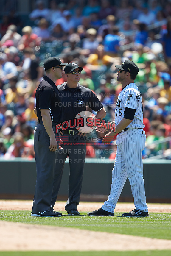 Charlotte Knights manager Mark Grudzielanek (15) discusses a call with first base umpire Shane Livensparger (center) and second base umpire Adam Beck during the game against the Gwinnett Stripers at BB&T BallPark on May 2, 2018 in Charlotte, North Carolina.  The Knights defeated the Stripers 6-5.  (Brian Westerholt/Four Seam Images)