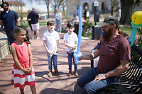 Jonni Crite, 5, of Bella Vista (from left)watches Anthony Kellington of Eureka Springs make a balloon sword, Sunday, April 4, 2021 at the downtown square in Bentonville. Check out nwaonline.com/210405Daily/ for today's photo gallery. <br /> (NWA Democrat-Gazette/Charlie Kaijo)