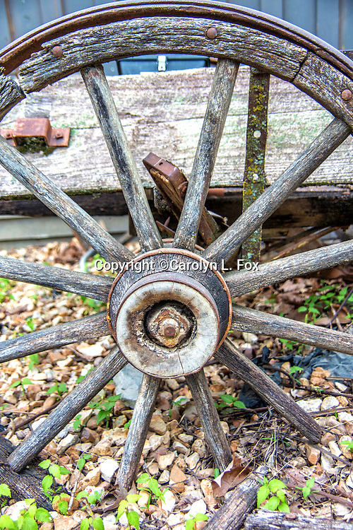 An old wheel sits by a building.
