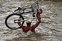 A contraband smuggler carries a bicycle through the river Tachira on the Colombia-Venezuela border, 3 May 2006. Venezuelan gasoline, being 20 times cheaper than in Colombia, is the most wanted smuggling item, followed by food and car parts, while reputable Colombian clothing flow to Venezuela. There are about 25,000 barrels of gasoline crossing illegally the Venezuelan border every day. The risky contraband smuggling, especially during the rainy season when the river rises, makes a living to hundreds of poor families in communities on both sides of the frontier.