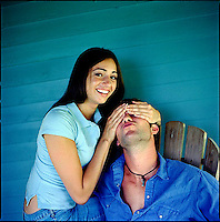 Woman, looking at camera, covering eyes of man looking next to her<br />