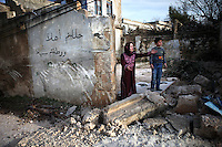 """SYRIA, 02.2012, village of Kureen, Idlib province. © Timo Vogt/EST&OST. A woman standing on her property destroyed by Syrian government troops. The Arabic words written on the wall mean """"welcome"""", which is common to write on the wall when someone returns from his Mekka pilgrimage. On February 22 the Syrian army attacked the village. Kureen was among the first villages in the northwest of Syria controlled by the opposition. Some villagers and members of the defence units escaped to surrounding olive orchards when the attack began in the early morning. A majority of the inhabitants didn´t manage to escape. The heavy shelling lasted 7 hours. Soldiers searched all houses, burnt some of them down, looted shops, stole cars and furniture. About 60 motorcycles were destroyed. Tanks demolished several houses. 6 men were executed. One woman died as a result of an heart attack."""
