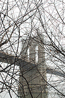 Brooklyn Bridge, Viewed thru Bare Trees on an Overcast Winter Day, New York City, New York State, USA