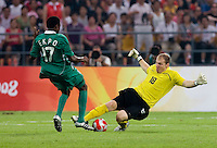 USMNT goalkeeper (18) Brad Guzan tackles nigerian midfielder (17) Emmanuel Ekpo outside the box while playing at Worker's Stadium.  The USMNT was defeated by Nigeria, 2-1, during the 2008 Beijing Olympics in Beijing, China.