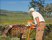 Senior male artist painting at an easel outdoors in Yellowstone National Park