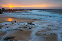 At sunset, a large wave recedes from the shore at Ke Iki on the North Shore of O'ahu.