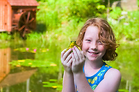 green frog, Lithobates clamitans, girl holding frog in front of pond in Andes, New York, Catskills