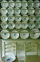 A pair of chairs sit beneath rows of blue and white plates  displayed on wall-to-wall plate racks in the china pantry