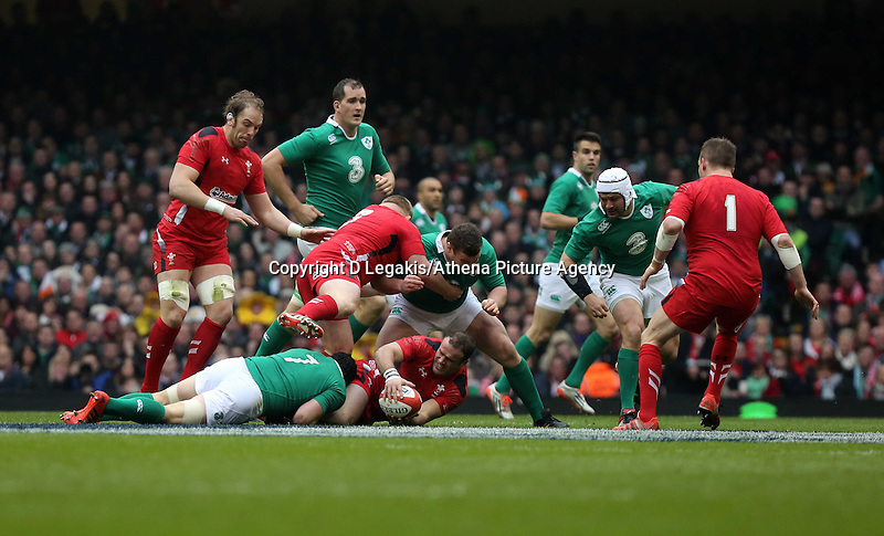 Pictured: Jamie Roberts of Wales (with ball) having just been brought down by Sean O'Brien of Ireland, while Samson Lee of Wales (3) pushes Jack McGrath of Ireland away Saturday 14 March 2015<br /> Re: RBS Six Nations, Wales v Ireland at the Millennium Stadium, Cardiff, south Wales, UK.