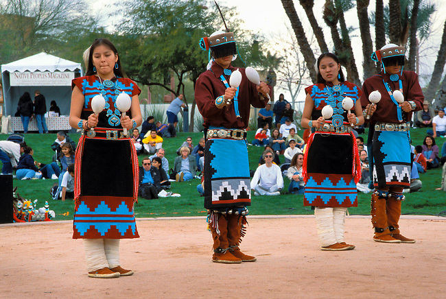 Group of Navajo youth dressed in traditional regalia practicing traditional songs while playing gourd rattles in Phoenix Arizona