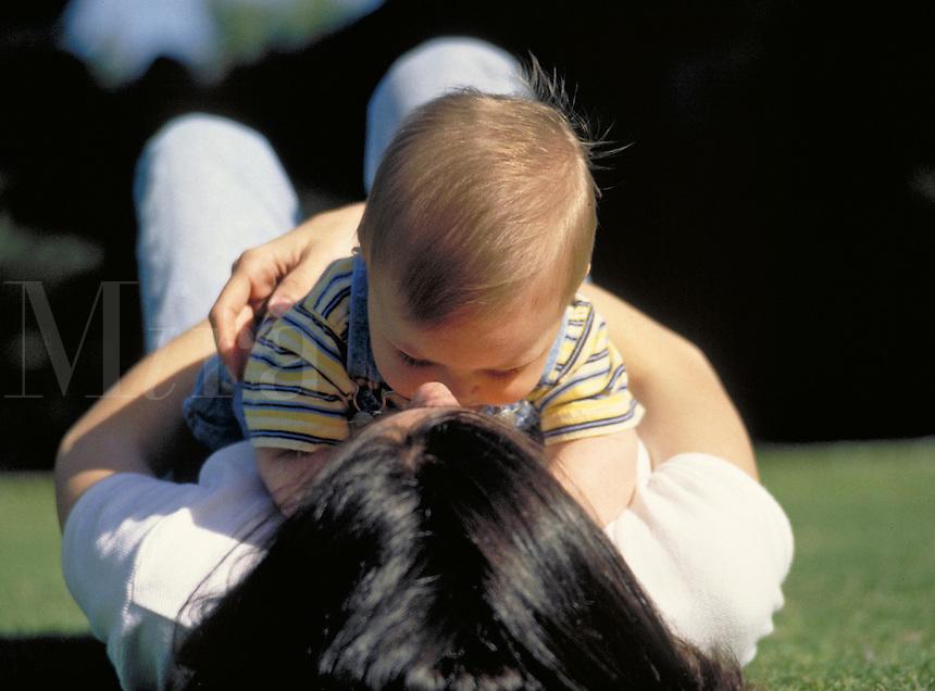 Mother, Christine, lying on her back embracing baby Alexander, kissing, love, affection, babies, motherhood, happy, playing. Alexander and Mom. Santa Monica California.