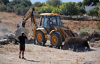 Pictured: A forensics officer takes pictures as diggers work to clear the new site of the search, where rubble was deposited from the farmhouse where Ben Needham disappeared from in Kos, Greece. Thursday 06 October 2016<br />Re: Police teams led by South Yorkshire Police, searching for missing toddler Ben Needham on the Greek island of Kos have moved to a new area in the field they are searching.<br />Ben, from Sheffield, was 21 months old when he disappeared on 24 July 1991 during a family holiday.<br />Digging has begun at a new site after a fresh line of inquiry suggested he could have been crushed by a digger.