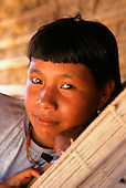Koatinemo village, Brazil. Smiling young Assurini Indian woman lying in a hammock.