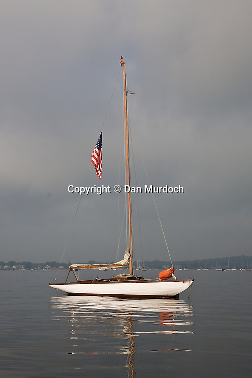 A wooden classic sailboat on a morning