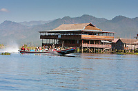 Myanmar, Burma.  Boat Taxi Passing Restaurant on Stilts, Inle Lake, Shan State.