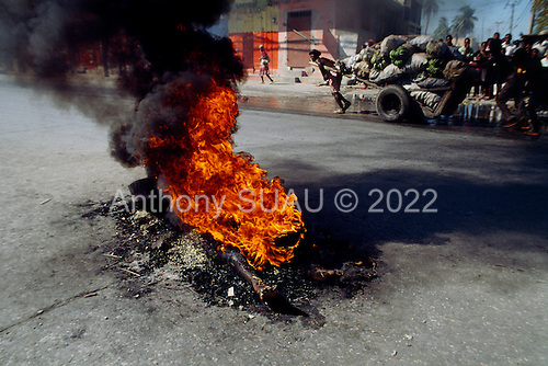 Port-au-Prince, Haiti<br /> November 25, 1987<br /> <br /> The street burning of a suspected ton-ton-macoute prior to elections being held on November 29th, the first attempt at a democratic election in Haiti. It was unsuccessful as 34 people were killed at a polling station and elections were moved up to February 1988.<br /> <br /> Leslie François Manigat won the election with many political parties boycotting. He had military backing but once in office he sought greater control over the military in an effort, to fight corruption. Manigat's government was overthrown by General Henri Namphy within months.