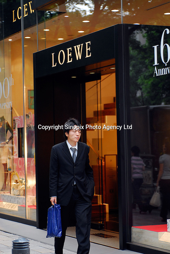 Shoppers walk past Loewe on Omotesando in the Harajuku area of Tokyo, Japan. As Japan is seeing the light after over ten years of a stagnant economy public consumer spending is on the increase with new shops and cafes opening and doing well..
