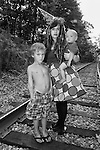 A mother clown standing on train tracks with her two children