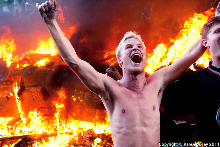An exuberant fan yells in front of a car lit by rioters shortly after the Canuck's were defeated by the Boston Bruins in the seventh game of the Stanley Cup in Vancouver, BC on June 15, 2011. (photo by Karen Ducey)