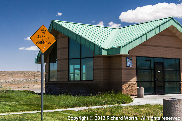 """A sign in a Utah desert rest area warns, """"Watch for SNAKES & SCORPIONS"""".  On the building, between Salt Lake City and the Bonneville Salt Flats, is another sign, """"Welcome to the Grassy Mountain East Rest Area""""."""