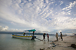 Men unload supplies from a boat for the tourist community on Gili Trawangan, Lombok, Indonesia.