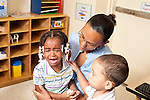 Education preschool  3-4 year olds teacher holding crying child on her lap nearby boy observing trying to give her a hug or a pat separation first days of school empathy horizontal