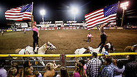 Two women fly the American Stars and Stripes flag while standing on horseback in a rodeo arena in Dodge CIty, Kansas...