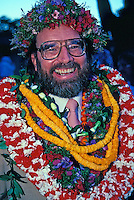 Portrait of a young Congressman Neil Abercrombie, bedecked with leis, after winning an election