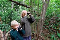 Mädchen und Junge, Kind, Kinder beobachten Vögel im Wald mit dem Fernglas