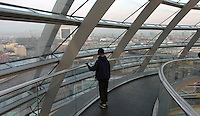 The Berlin skyline is seen from the dome at the top of the Reichstag building in Berlin December 28, 2008. Tourists visit The Reichstag building in Berlin photographed December 28, 2008. It was opened in 1894 and housed the Reichstag until 1933, when it was severely damaged in a fire supposedly set by Dutch communist Marinus van der Lubbe, who was later beheaded for the crime. The building remained in ruins until the reunification of Germany, when it underwent reconstruction led by internationally renowned architect Norman Foster. After its completion in 1999, it became the meeting place of the modern German parliament, the Bundestag. (Photo by Alan Greth)