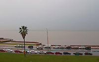 A view over the Rio de la Plata in Montevideo on a rainy day. Cars parked along the shore walk Rambla sur and Rambla Gran Bretagna along the River Rio de la Plata Montevideo, Uruguay, South America