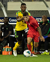 NASHVILLE, TN - JULY 3: Devon Williams #22 attempts to slow down Christian Pulisic's #10 run during a game between Jamaica and USMNT at Nissan Stadium on July 3, 2019 in Nashville, Tennessee.