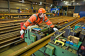 A worker in the Points and Crossings Shed of London Underground's  Lillie Road Depot bends a replacement rail to match a curve in the track.  The depot produces replacement track for the tube network and offers a same day service for 'urgencies and emergencies'.  The depot is now run by London Underground following the collapse of PPP contractor Metronet in 2007.