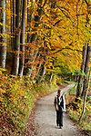 Deutschland, Bayern, Oberbayern, junge Frau beim Spaziergang durch Herbstwald, allein | Germany, Bavaria, Upper Bavaria, young woman walking through autumn forest