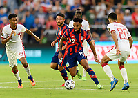 AUSTIN, TX - JULY 29: Eryk Williamson #19 of the United States keeps the ball away from Homam Ahmed #14 and Abdullah Al Ahrak #20 of Qatar during a game between Qatar and USMNT at Q2 Stadium on July 29, 2021 in Austin, Texas.