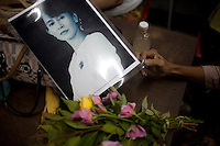 A National League for Democracy (NLD) supporter holds Nic Dunlop's iconic image of Aung San Suu Kyi, as they wait inside the party HQ, ahead of the imminent release of The Lady from house arrest in Rangoon. From 1990 until her release on 13 November 2010, Aung San Suu Kyi had spent almost 15 of the 21 years under house arrest.