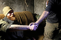 """UKRAINE, 02.2016, Oblast Donetsk. Ukrainian-Russian conflict concerning Eastern Ukraine / Foreign volunteers (""""Task Force Pluto"""") fighting with the far-right militia Pravyi Sektor against the Russian-backed separatists: Craig (USA) and Ben (Austria) pose with the jointly tattooed Greek quote """"Molon Labe"""" (come and take them) on their arms. © Timo Vogt/EST&OST"""