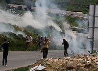 Under a cloud of tear gas residents of the Palestinian village Nabi Saleh, Israeli and international activists run away during the weekly demonstration against Israeli settlement expansion, in the West Bank village of Nabi Saleh, near the Jewish settlement of Halamish, Photo by Quique Kierszenbaum