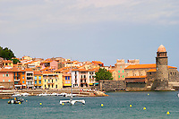 The church Eglise Notre Dame des Anges, our lady of the angels. With its emblematic church tower. The beach in the village. Colourful houses along the water. Collioure. Roussillon. France. Europe.