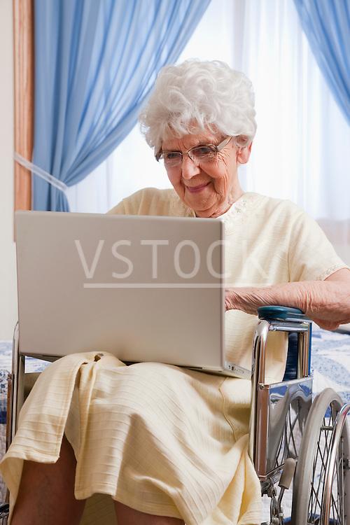 USA, Illinois, Metamora, Senior woman on wheelchair using laptop