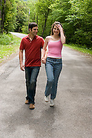 Young couple walking down country road holding hands<br />