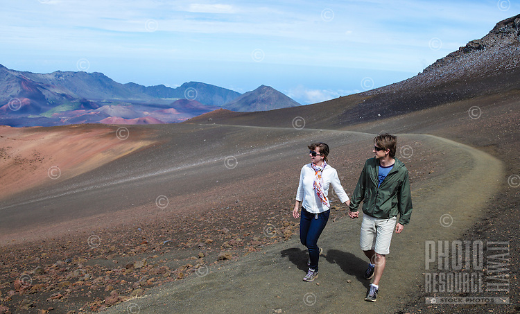 A young couple takes in the view while hiking the the Sliding Sands Trail at Haleakala National Park on Maui.