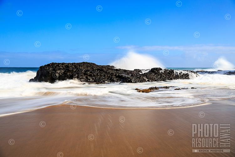 A long exposure image of waves jumping and circling around a large volcanic rock at Lumaha'i Beach, Kaua'i.
