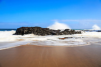 A long exposure image of waves jumping and circling around a large volcanic rock at Lumaha'i Beach, Kaua'i.