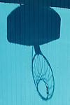 Reflection of a basketball net on a blue garage door, Santa Monica, California